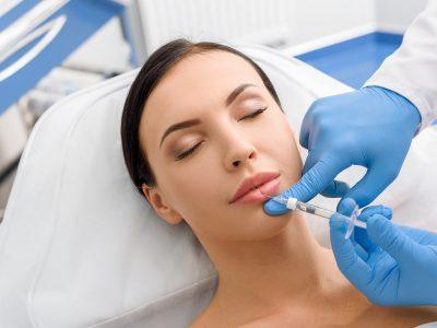 donna che sta facendo un trattamento estetico filler alle labbra attraverso l'uso di aghi in un centro specializzato evitando le soluzioni fai da te